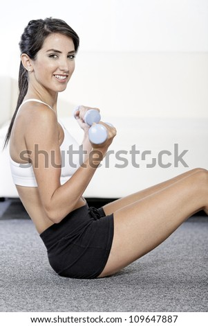 Beautiful young woman training with weights at home