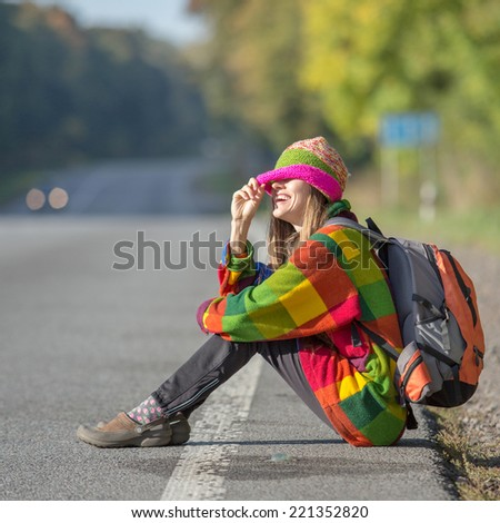 Beautiful young woman traveling sitting on road happy smiling. daylight, shadows