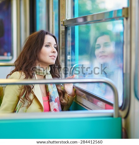 Beautiful young woman travelling in a train of Parisian underground and looking through the window
