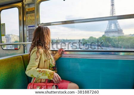 Beautiful young woman travelling in a train of Parisian underground and looking through the window at the Eiffel tower - stock photo