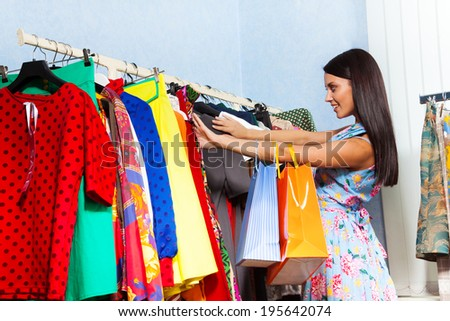 Beautiful young woman try to find clothes in shop - stock photo