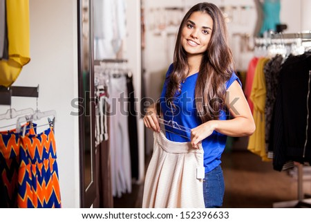 Beautiful young woman trying on a new skirt in a clothing store, in front of a mirror
