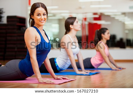 Beautiful young woman trying the cobra pose and smiling during yoga class - stock photo
