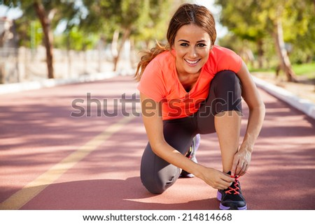 Beautiful young woman tying her shoes before going for a run at a track on a sunny day - stock photo
