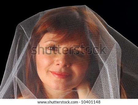 Beautiful young woman under a gauzy veil - stock photo