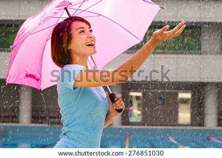 Beautiful young woman under pink umbrella - stock photo