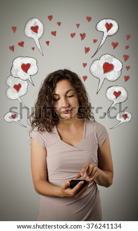 Beautiful young woman using a mobile phone. Valentine day. - stock photo