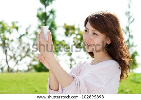 Beautiful young woman using a moblie phone in a park. Portrait o - stock photo