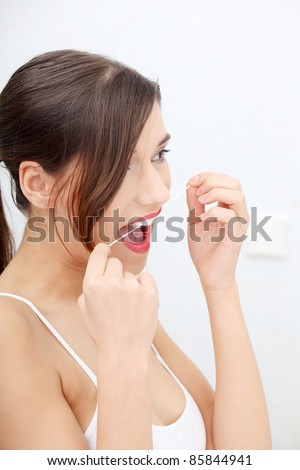 Beautiful young woman using dental floss at bathroom