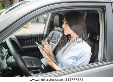 Beautiful young woman using digital tablet  in a car