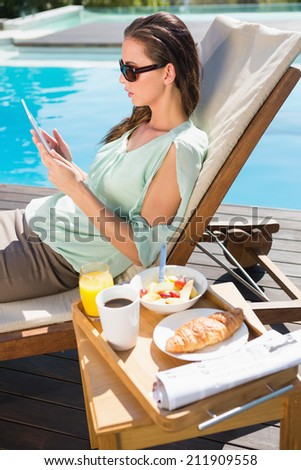 Beautiful young woman using digital tablet with breakfast on table - stock photo