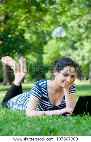 Beautiful young woman  using her laptop outdoors in a park