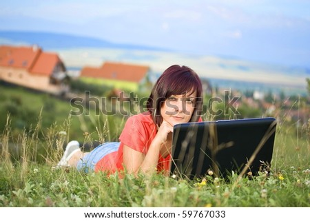 Beautiful young woman using laptop at outdoor - stock photo