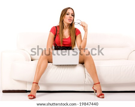 Beautiful young woman using laptop on couch. - stock photo