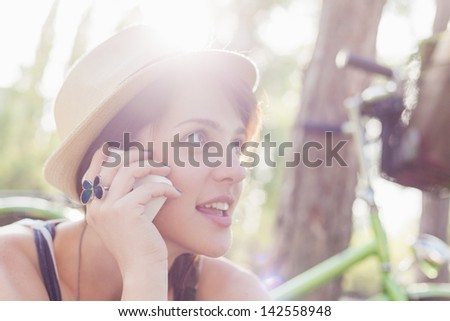 Beautiful young woman using mobile phone next to her bike. - stock photo