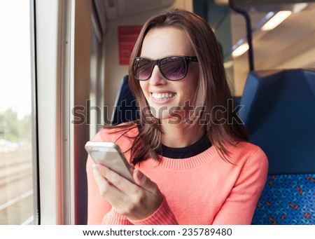 Beautiful young woman using mobile smart phone on train - stock photo