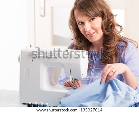 Beautiful young woman using sewing machine at home - stock photo