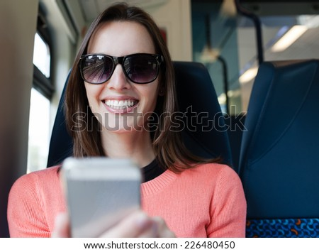 Beautiful young woman using smart phone mobile in the train - stock photo