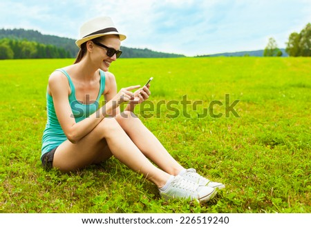 Beautiful young woman using smart phone mobile outdoors - stock photo
