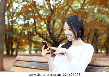 Beautiful young woman using smart phone on a bench in autumn park