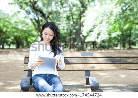 Beautiful young woman using tablet computer on a bench in the park - stock photo