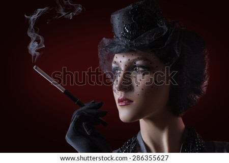 Beautiful young woman vintage retro style studio portrait, smoking.