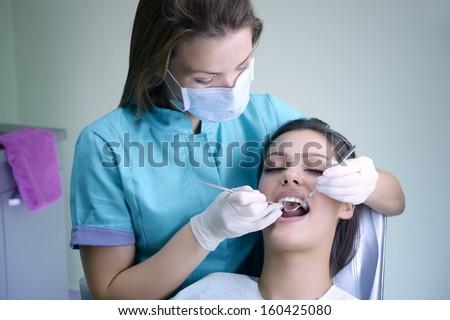 beautiful young woman visiting dentist for dental checkup - stock photo