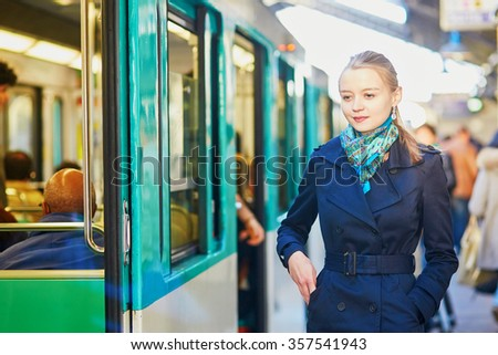 Beautiful young woman waiting for a train on the platform of Parisian underground