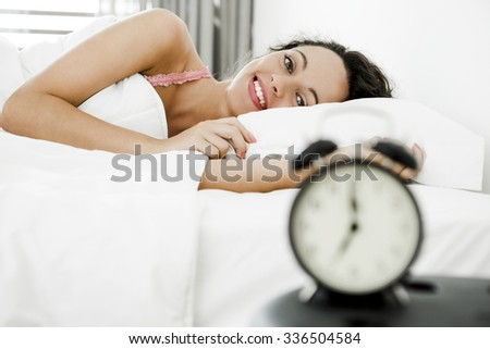 Beautiful young woman waking up with the alarm clock - stock photo