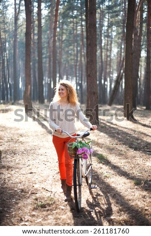 Beautiful young woman walk with retro bike with tulips in basket in sunny park