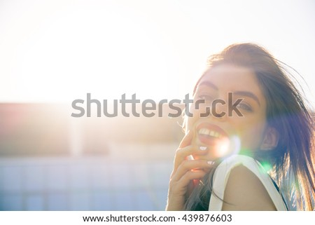Beautiful, young, woman walking across the street, modern building in the background, lens flare