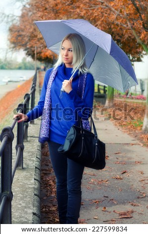Beautiful young woman walking beside river on rainy autumn day. - stock photo