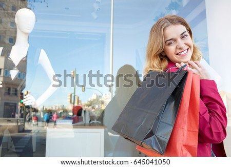 Beautiful young woman walking by fashion clothing store, looking smiling at camera in city street carrying shopping bags. Consumer recreational lifestyle. Female buying, with manikins in background.