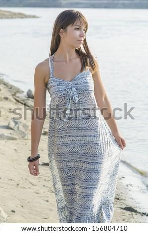 Beautiful young woman walking down the beach. - stock photo
