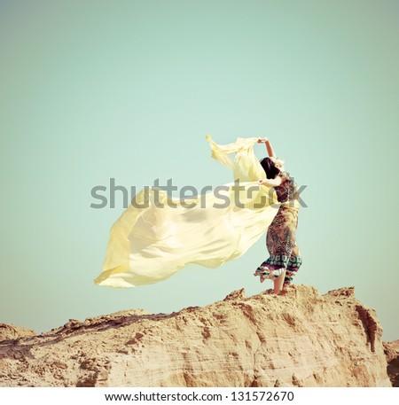 Beautiful young woman walking in a desert - stock photo