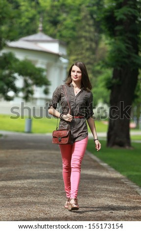 Beautiful young woman walking in a park in summer - stock photo