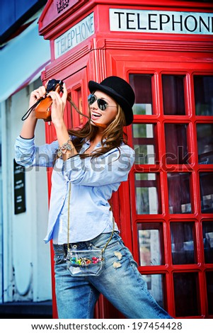 Beautiful young woman walking in the city and photograghs. Europe, England. Vacation, tourist trip. - stock photo