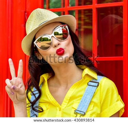 Beautiful young woman walking in the city. Europe, England. Vacation, tourist trip. Fashion woman in sunglasses outdoor.Blowing lips kiss. - stock photo