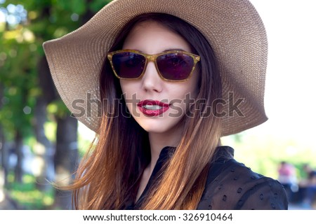 Beautiful young woman walking in the city. Fashion portrait.Portrait of beautiful young woman with hat.Beautiful young woman in elegant hat and sunglasses posing outdoor.Sexy young woman with red lips - stock photo