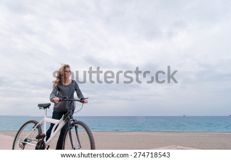 Beautiful young woman walking near the sea with bicycle against sky background.