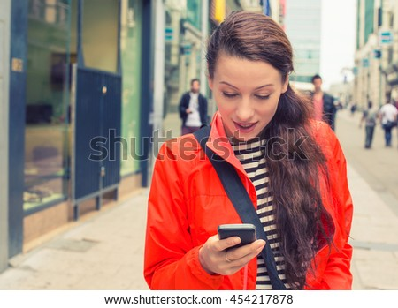 Beautiful young woman walking on a city street and using her mobile phone