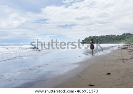 Beautiful young woman walking on a lonely beach in the Costa Rican south pacific