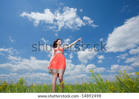 Beautiful young woman walking on field enjoying wind wave pointing out - stock photo