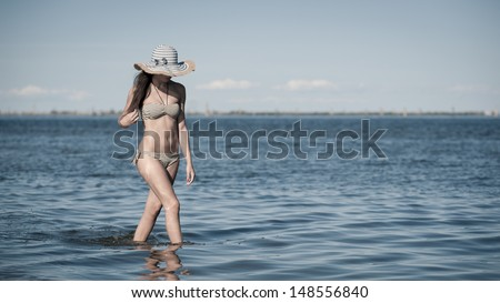 Beautiful young woman walking on the beach.