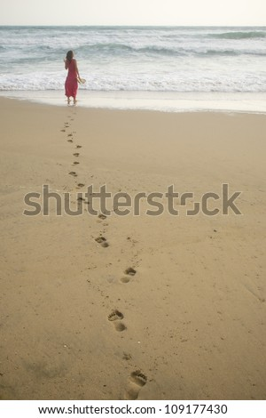 Beautiful young woman walking on the beach towards the sea leaving footprints - stock photo