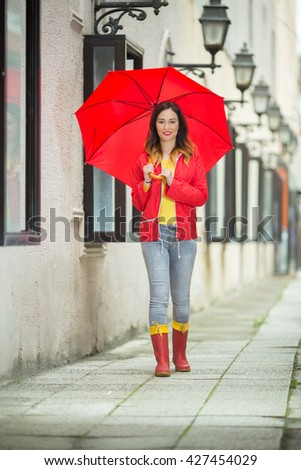 stock photo beautiful young woman walking on the city street with red umbrella wearing red raincoat and rubber 427454029