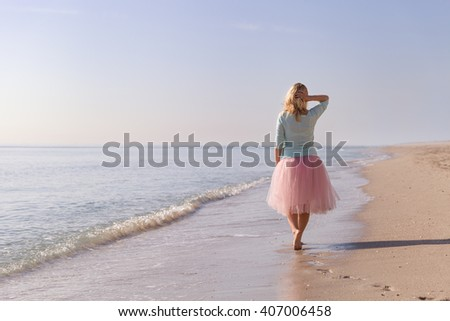 Beautiful young woman walking on the sandy ocean beach. Summer sea vacations. Smiling girl on the beach. Happy woman enjoying vacation. - stock photo