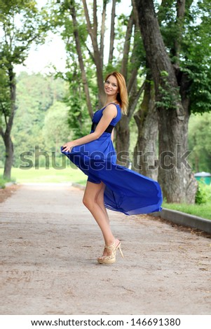 Beautiful young woman walking on the summer park - stock photo