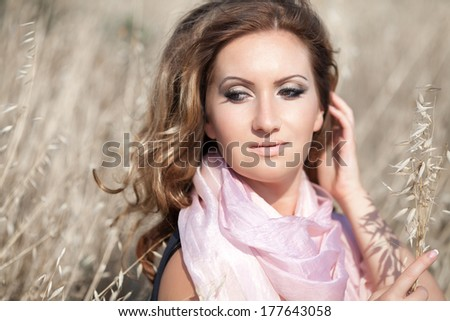Beautiful young woman walking outdoors lifestyle portrait. Skin care and beauty concept. Happy girl in wheat field in summer. Healthy woman life. series.