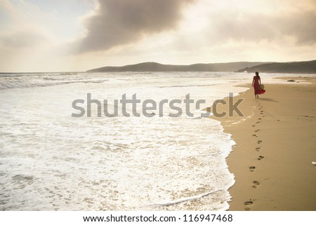 Beautiful young woman walks along the surf on a pristine sandy beach - stock photo